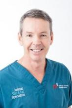 Dr Greg Burton smiles to camera in his blue scrubs